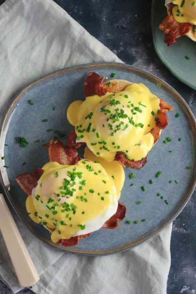 Eggs Benedict - two poached eggs layered on slices of bacon on a slice of English Muffin, topped with yellow hollandaise sauce and sprinkled with chopped chives.