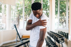 suffering from shoulder pain during workout with dumbbells