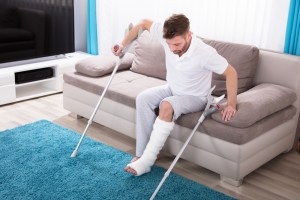 Man With Broken Leg Using Crutches To Get Up From Sofa
