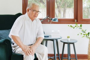 senior man sitting down experiencing knee pain due to osteoarthritis