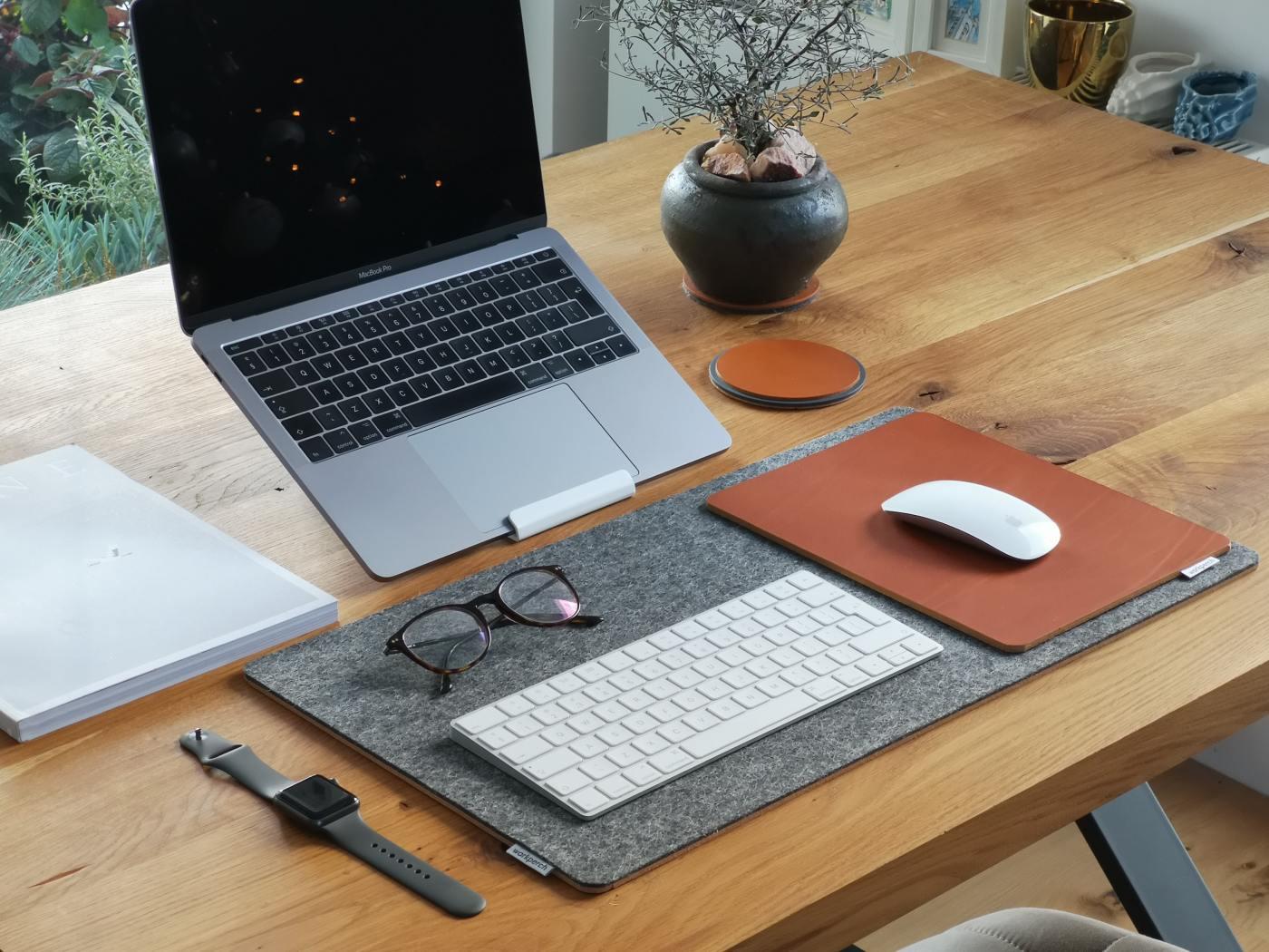 Scrivania da lavoro arredata con pc, sottomano e tanto altro