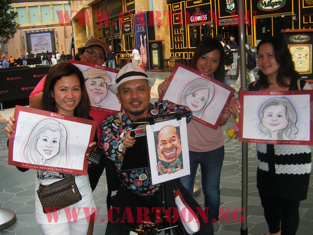Caricaturist taking pictures with satisfied customers at Resort World Sentosa