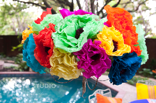Paper flower chandelier with a pool in the background