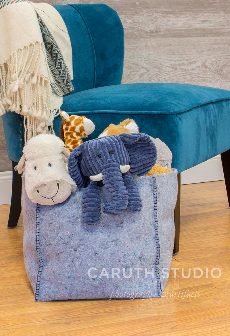 light blue felt toy box filled with stuffed animals set in front of a blue velvet chair