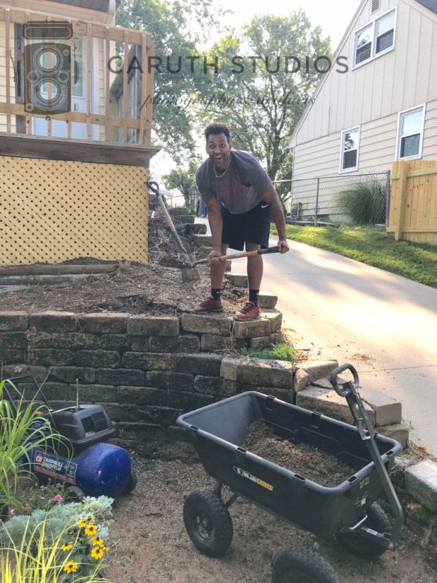 andrew digging for plants in retaining wall