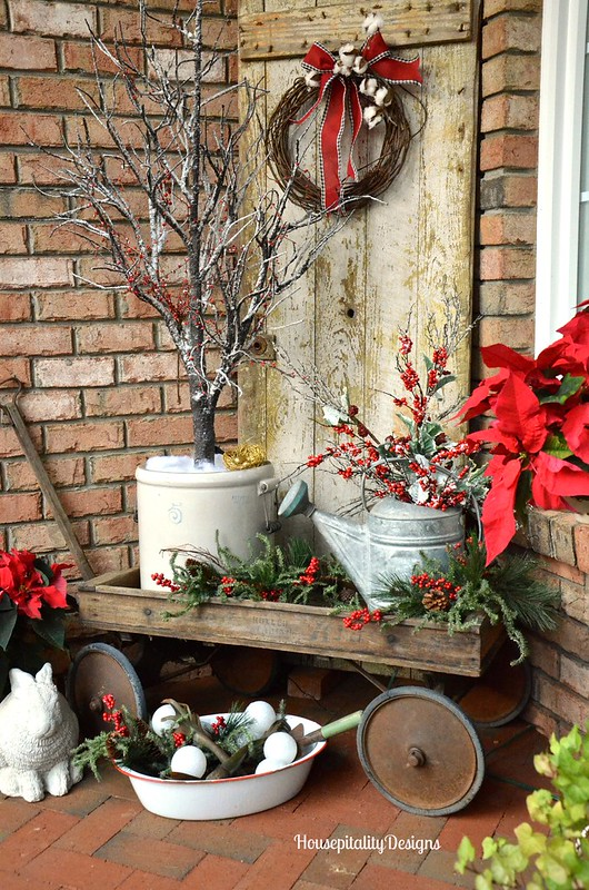 ceramic and metal containers in a wooden wagon with holiday plantings