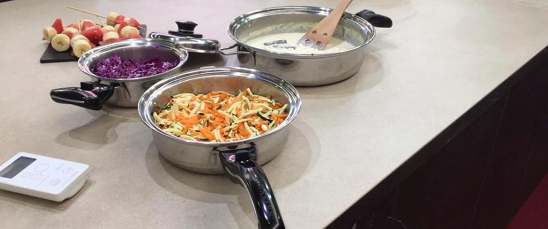 Casa Interior Cooking Rak: Encimera con sartenes y ollas y el control remoto de la placa.