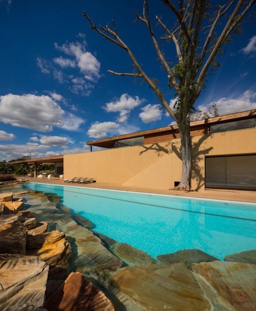 Pedras naturais rústicas são utilizadas no paisagismo dessa piscina. Casa Ao Cubo. Foto: Fernando Guerra.
