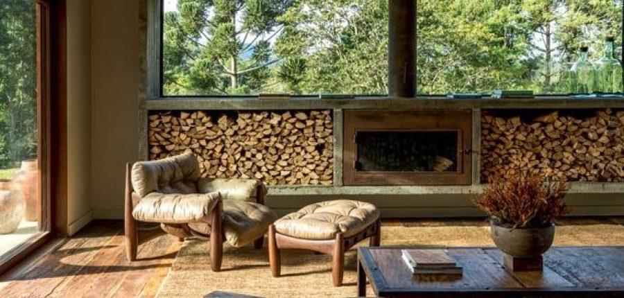 Sala com decoração rústica. Piso de madeira, lareira, lenha. Mesa de centro em madeira rústica. Poltrona Mole, de Sergio Rodrigues. Grandes panos de vidro trazem o aconchego da natureza para dentro da casa.