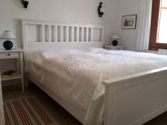 Ein Schlafzimmer mit breitem Doppelbett.