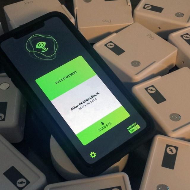 Pra cego ver: Foto mostra um celular com o aplicativo Veever em funcionamento. O aparelho está em cima de embalagens como se fossem caixas. — Foto: Veever/Divulgação