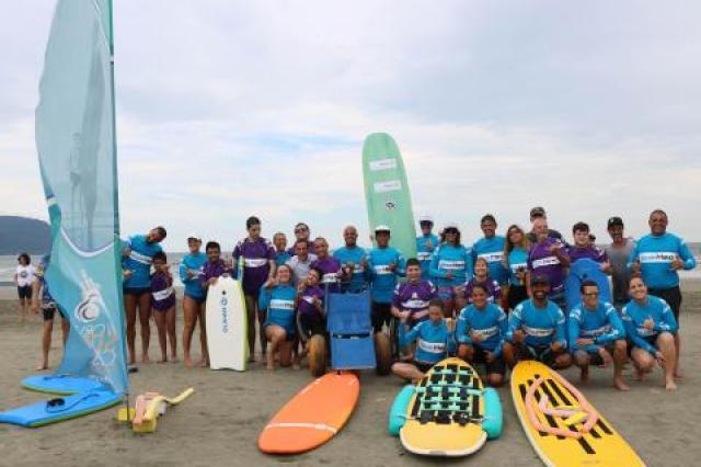 grupo de surfistas posa com pranchas na praia #pracegover