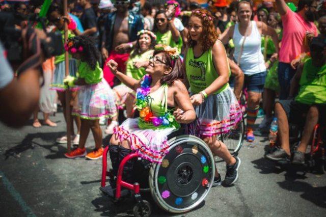 Integrante da bateria inclusiva do bloco de carnaval Chama o Síndico desfilando em cadeira de rodas pela avenida