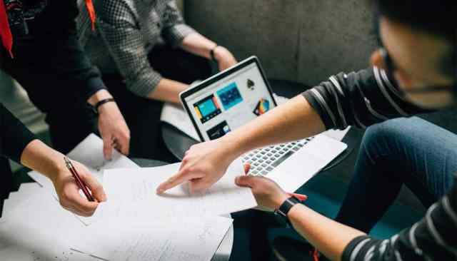 Fotografia de três pessoas sentadas ao redor de duas mesinhas. Sob as mesas há um laptop aberto e diversas folhas de papel espalhadas. Uma das pessoas segura uma caneta, e a outra aponta para um local específico do papel.