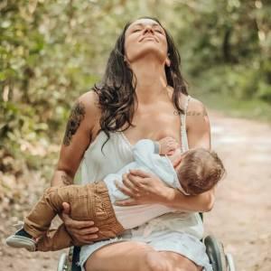 Em um jardim, mulher de pele branca e cabelos castanhos e ondulados está sentada em uma cadeira de rodas e amamentando um bebê. Ela está com os olhos fechados e com a cabeça inclinada para trás. Ela usa um vestido branco de alça e o bebê uma calça caramelo e uma camisa branca.