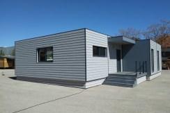 Casa modular moderna cúbica Lara con revestimiento en Cedral Lap Wood, color gris y acero