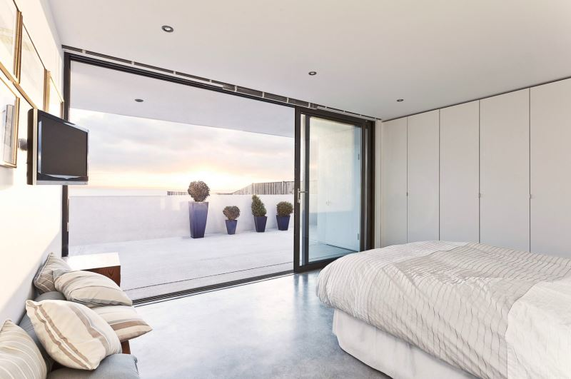 Modern-bedroom-with-a-balcony-view-of-plants