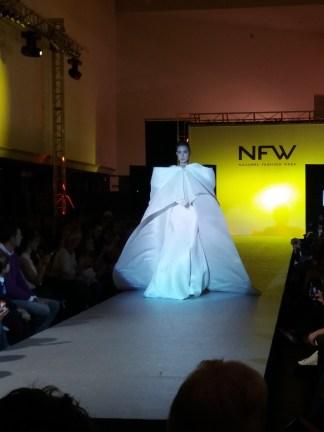 Vista delantera del último vestido del desfile, de corte sirena, escote drapeado y capa con cola. ALICIA ARZA.