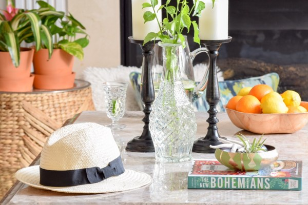 Style the coffee table with fresh garden clippings in thrifted decanter and fresh fruit in a wooden bowl
