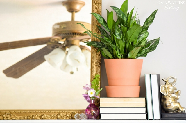 Create an eclectic summer mantel look with gold mirror, plant, and vintage books