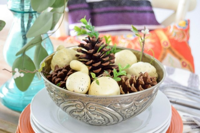 Use a silver bowl for fall centerpiece with pinecones, pumpkins, and greenery