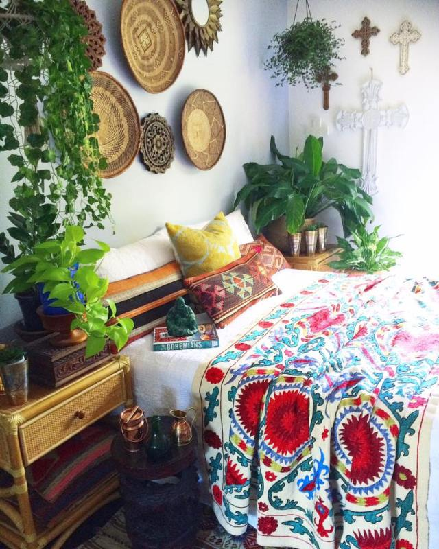 Colorful suzani blanket with basket wall decor in global boho bedroom of La Boheme House