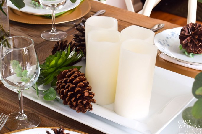 use stacked white platters with candles and pinecones for centerpiece