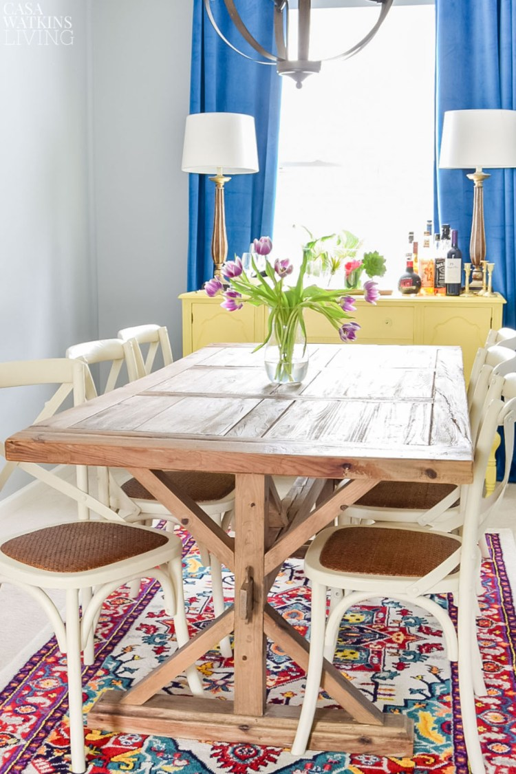 Velvet drapes with farmhouse table and colorful rug