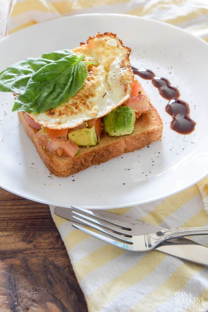 avocado and tomato toast with egg, basil, and balsamic glaze