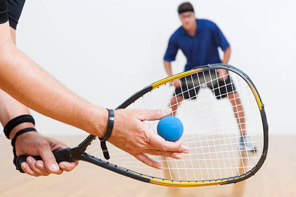 Two men playing racquetball on court. One serving.
