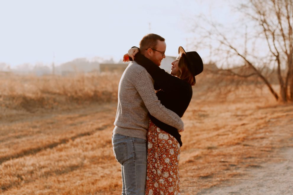 A couple embracing near some fields