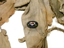 A school pin on the tattered remains of a school uniform worn by a girl on the day of the bombing.