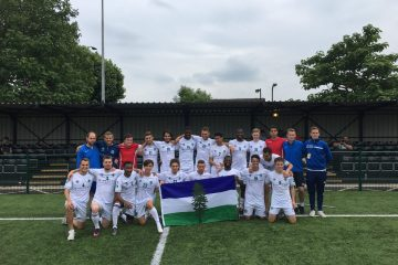 Team Cascadia 2018 poses for a photograph on a soccer field in London England following the CONIFA World Cup 2018. They're holding a Cascadian flag and are flanked by Team Cascadia coaches in blue.
