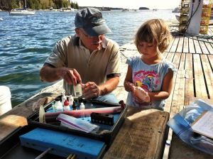 Athena assisting her grandfather Don Gower with his water quality monitoring.