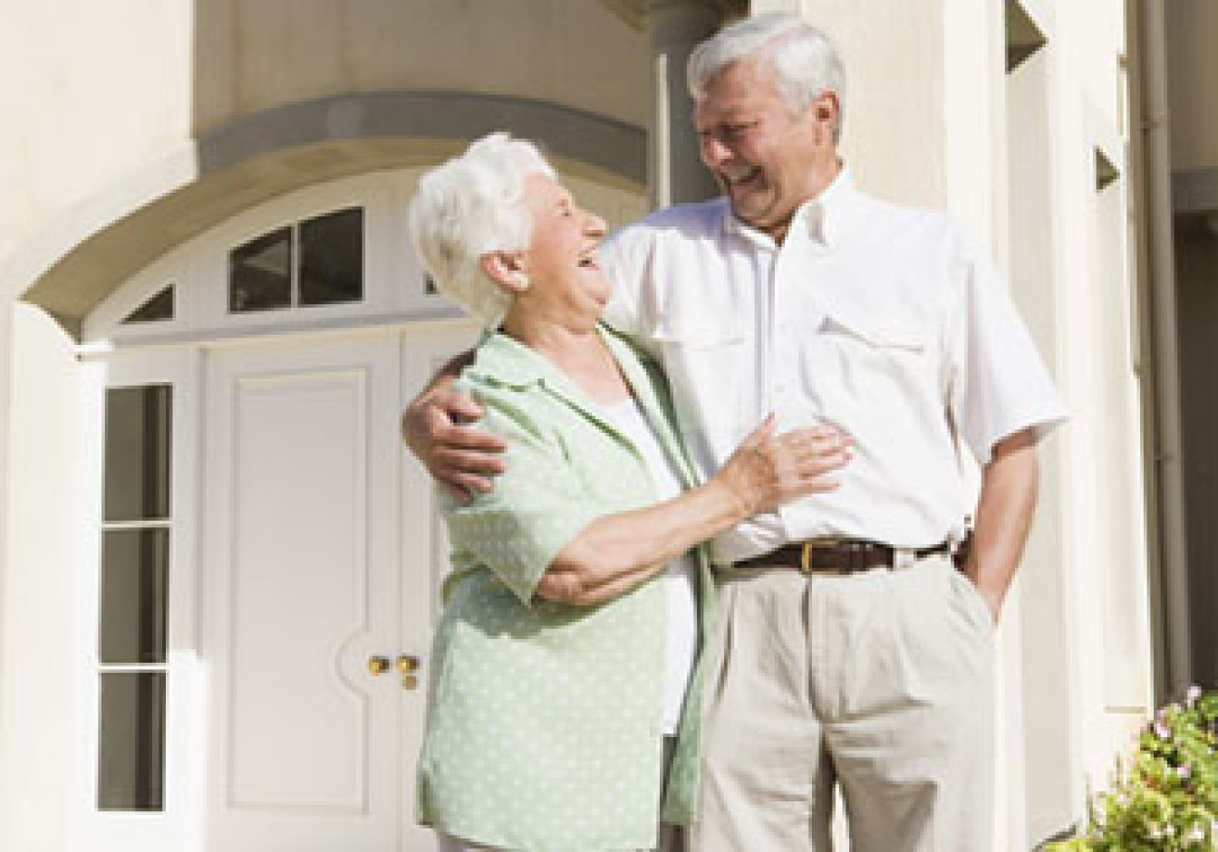 Couple smiling in front of house