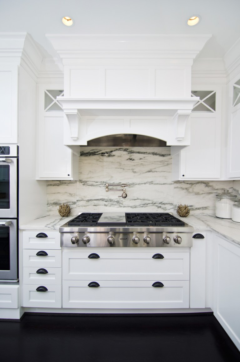 bright kitchen stove top wood paneled hood marble backsplash wall mounted potfiller