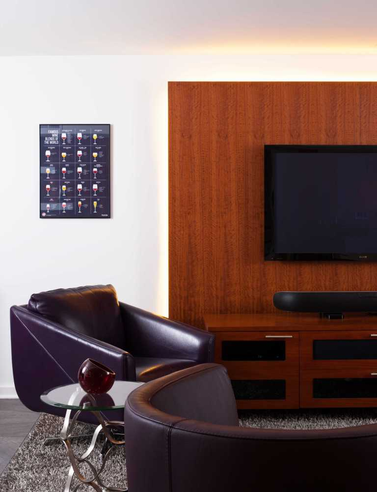 modern style built in entertainment area natural wood wall feature and wall mount tv leather chairs