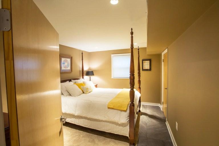 renovated basement bedroom yellow color tones cement floor