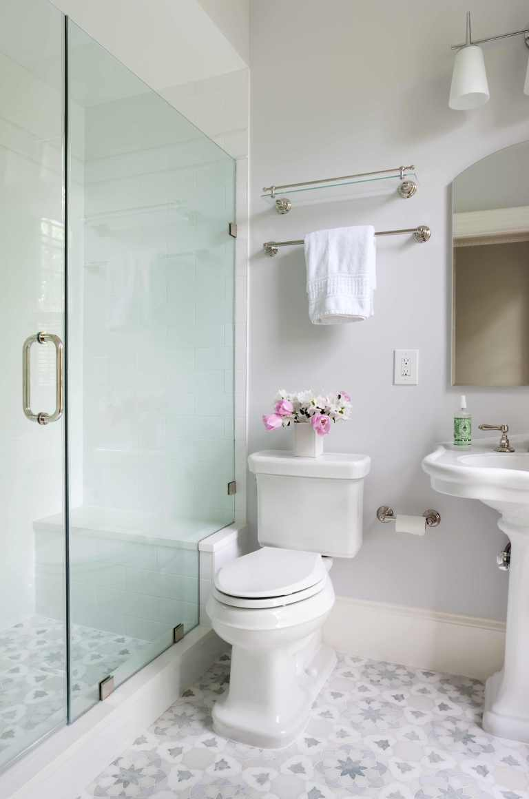 neutral color palette bathroom shower with glass door geometric mosaic tile floor design