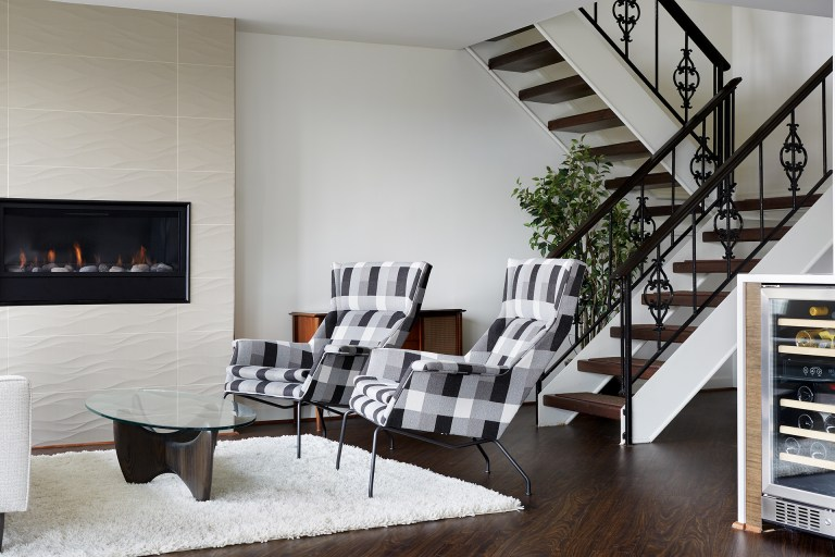 modern living room renovation textured fireplace open stairs black and white