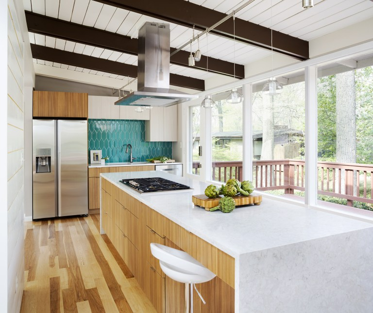 modern kitchen natural wood cabinetry and floors waterfall edge countertops teal tile backsplash beam ceiling