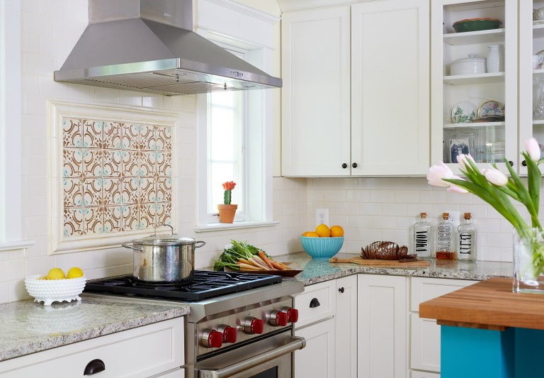 kitchen with white outer cabinetry and teal island cabinetry teal and orange mosaic tile backsplash behind stainless steel gas range