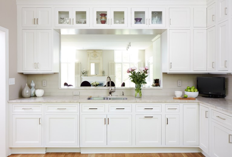 kitchen with wood floors and white cabinetry passthrough into dining area
