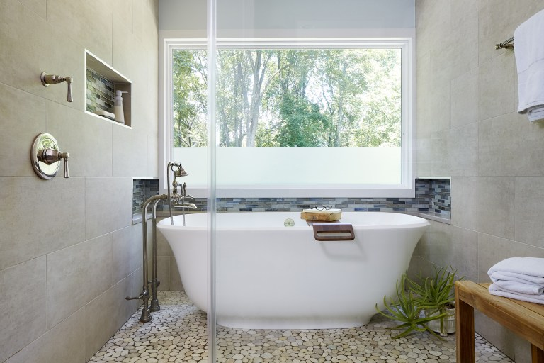 shower area with glass wall and freestanding tub green and neutral color palette relaxing