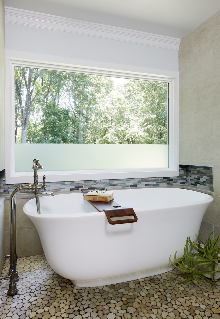 freestanding bathtub under window with partially frosted glass pebble tile outdoor vibe