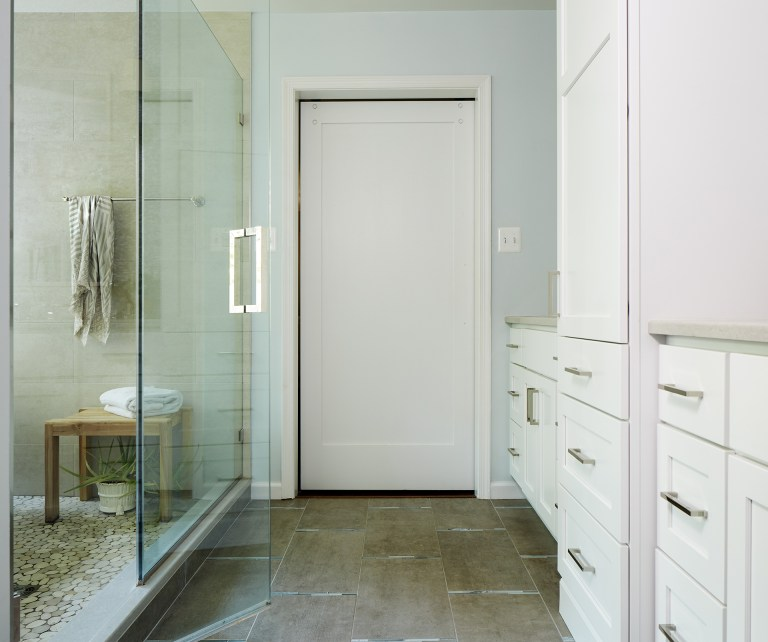renovated bathroom with lots of storage white cabinetry and shower area with glass wall