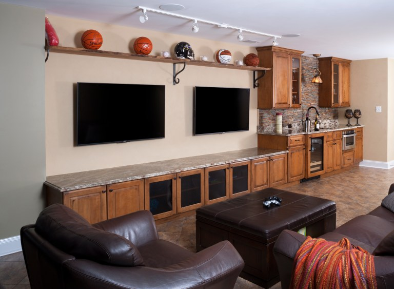 basement man cave entertainment center with open shelving and minibar area with beverage refrigerator