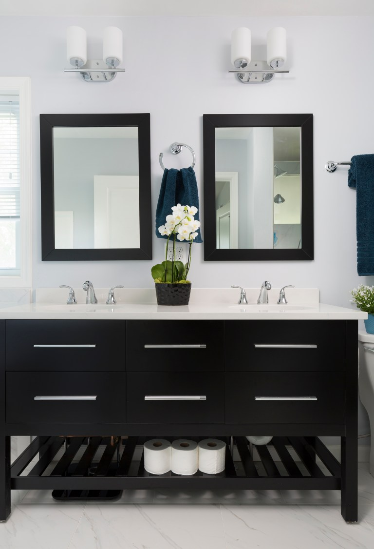 black bathroom vanity with double sinks and open shelving underneath white walls sconce lighting chrome fixtures