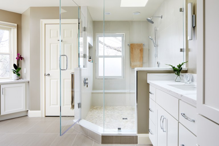 master bathroom renovation white color palette large shower with glass door window skylight and storage nooks built into walls white cabinetry plenty of storage