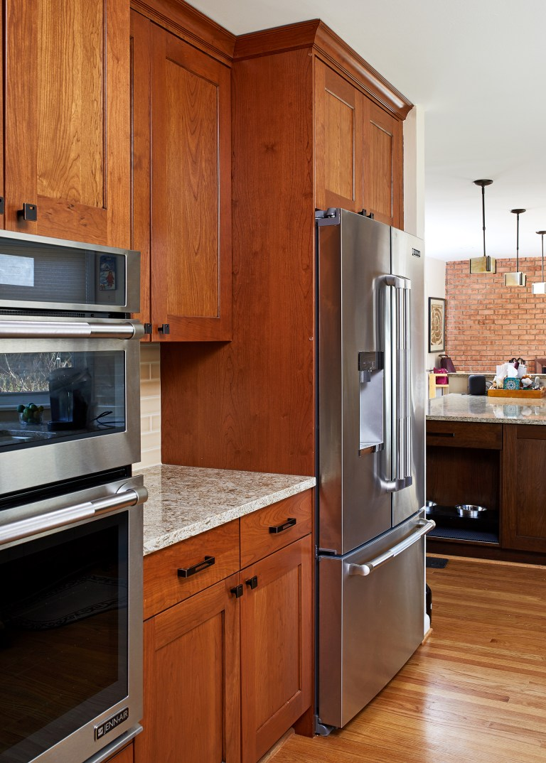 warm tone kitchen natural wood medium stain cabinetry stainless steel appliances